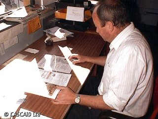 A man is sitting at a long table, looking at some paper documents.