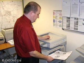 A man is removing a piece of paper from a photocopier.