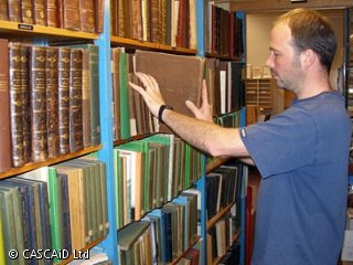 A man is removing a very old-looking book from a row of shelves.  The shelves are full of similar books.