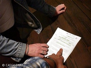 Two people are standing next to a table, pointing at a piece of paper.