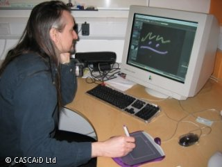 A man is sitting at a desk, using graphic design software on a computer.