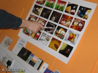 Somebody is pointing at a series of small images, placed on a wall.