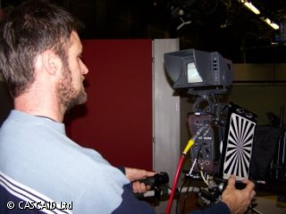 A man is looking at a large television studio camera.