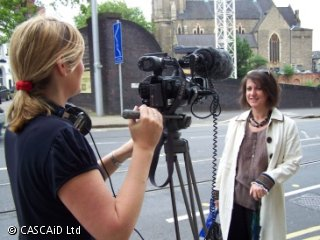 A woman is standing in a street, behind a television camera.  Another woman is standing in front of the camera and speaking.