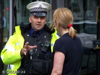 A woman is standing in a street, talking to a policeman.