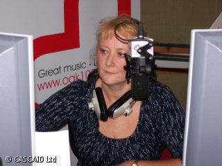A woman is sitting at a desk, in a radio studio.  She is speaking into a large microphone.