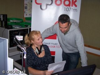 A woman is sitting at a control desk.  She has a pair of headphones around her neck.  A man is standing next to her, and they are both looking at a sheet of paper.