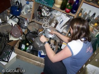 A woman is standing in a room, full of cluttered shelves and boxes.  She is removing an old kettle from a box.