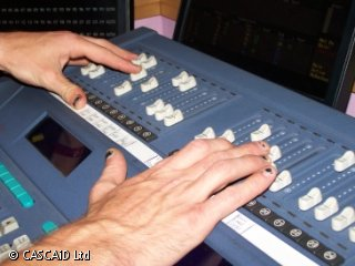 In close up, a man moves some switches on a lighting control desk.