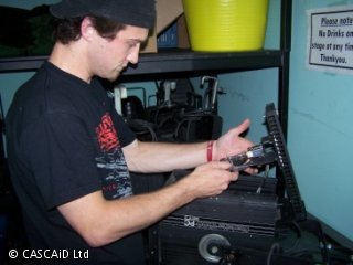 A man is standing next to a workbench.  He is adjusting a large stage light, which is on the bench.