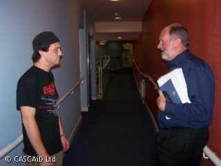 Two men are standing in a corridor, talking.