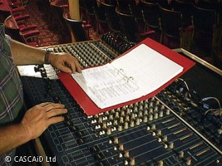 A man is standing at a sound control desk, which is full of buttons and switches. He is looking at an open folder.