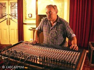 A man is standing at a sound control desk.  The desk is full of buttons and switches.