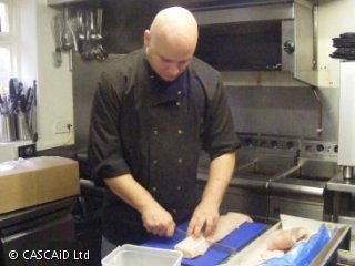 A man in a black chef's uniform is standing in a kitchen, cutting a large piece of fish with a sharp knife.