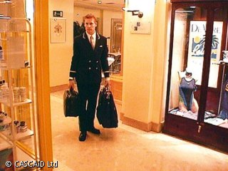 A man, wearing a hotel uniform, is carrying two suitcases down a corridor.