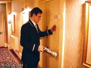 A man, wearing a smart hotel uniform, is knocking on the door of a hotel room.  He is holding a newspaper.