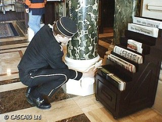 A man, wearing a smart hotel uniform, is crouching down and wiping a large marble pillar, with a cloth.