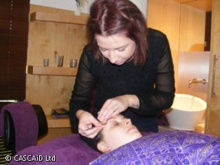 A lady is lying on a treatment couch with a purple cover over her.  A beauty therapist is standing behind the couch, plucking the lady's eyebrows with tweezers.
