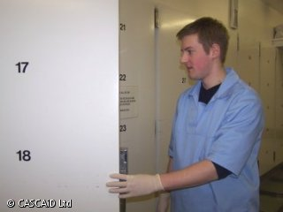 A man, wearing surgical clothing and latex gloves, is opening the door of a large refrigerator.