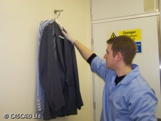 A man in surgical clothing is reaching up to retrieve a suit and shirt which are hanging on a hook.
