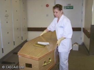 A woman in surgical clothing is placing the lid on a coffin.