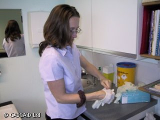 A woman is standing in a doctor's surgery.  She is putting on some latex gloves.