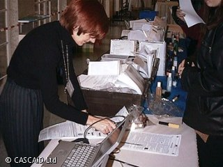 A woman is standing at a desk in a busy office.  She is using a computer.