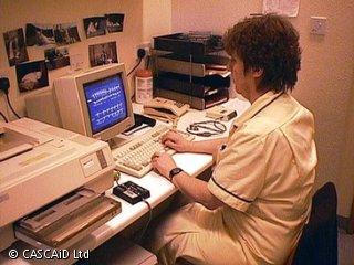 A woman, wearing a white medical uniform, is sitting at a desk, using a computer.