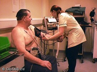 A woman, wearing a white medical uniform, is measuring the blood pressure of a man sitting in front of her.