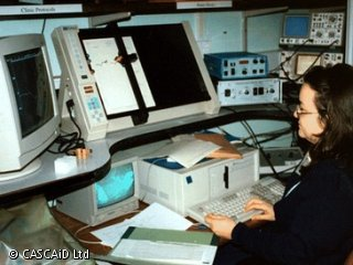 A woman is sitting at a desk in a laboratory.  She is using a computer.