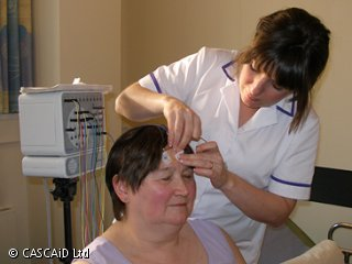A woman, wearing a medical uniform, is standing next to a seated woman.  She is placing electrodes on the woman's head.