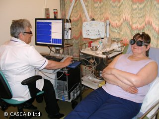 A woman is lying on a hospital bed.  She is wearing black goggles, which are plugged into a machine.  A man, wearing a white medical uniform, is sitting next to her.  He is looking at a monitor.