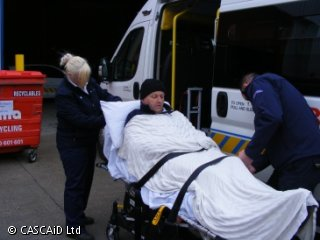 A man is sitting up on a stretcher.  A woman is standing behind him, adjusting the stretcher's headrest.  A man is fastening a safety strap around the stretcher.