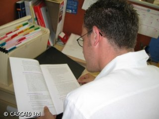 A man is sitting at a desk, reading a paper document.