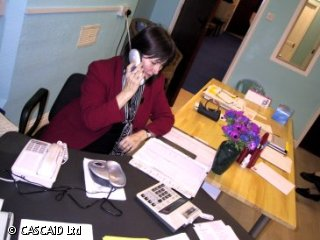 A woman is sitting at a desk, speaking on a telephone.