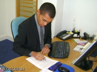 A man is sitting at a desk, writing on a printed document.