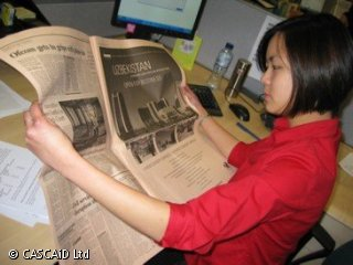 A woman is sitting at a desk, reading a broadsheet newspaper.