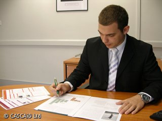 A man is sitting at a table, looking at something on a printed paper document.  He is holding a pen.