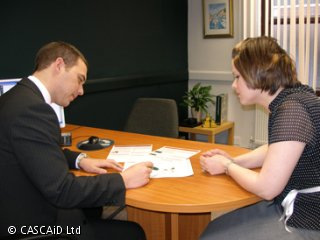 A man and a woman are sitting at a table in an office.  They are looking at some paper documents and the man is pointing to something on one of them.