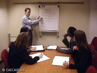 A man is standing at the front of a room.  He is using a flipchart.  Four people are sitting at a table in front of him.  They are watching him, and writing on notepads.