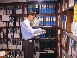 A man is standing in front of rows of floor-to-ceiling shelves, full of files and folders.  He is looking at the contents of a file.