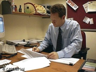 A man is sitting at a desk in an office.  He is writing on a paper document.