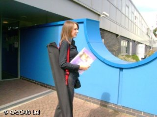 A woman is walking out of a building.  She is carrying some leaflets and has a long bag over her shoulder.