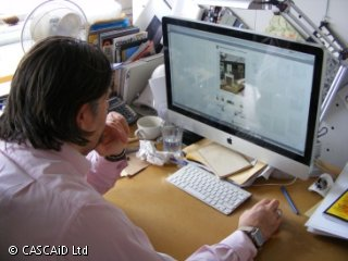 A man is sitting at a desk, looking at a photo on a computer screen.