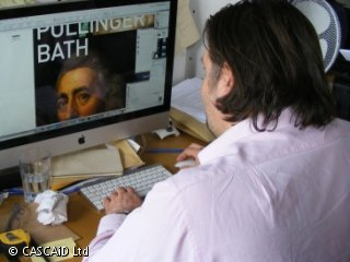 A man is sitting at a desk, adding large text to an image of a man's face on a computer screen.