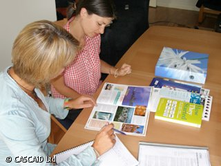 Two women are sitting at a table, looking at a colourful brochure.