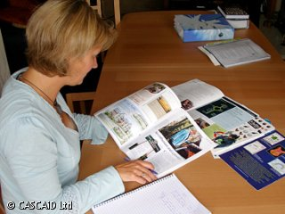 A woman is sitting at a table, looking at some magazines.