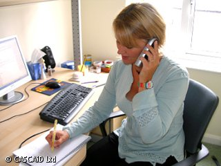 A woman is sitting at a desk, speaking on a telephone.  She is writing on a notepad.