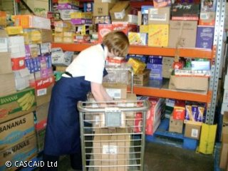 A woman is loading boxes on to a trolley in a warehouse.