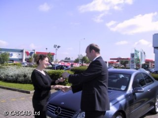A man and a woman are standing outside a car showroom.  There is a car behind them.  They are shaking hands, and the man is giving the woman a set of keys.